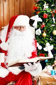 Santa Claus with book sitting in comfortable rocking chair near Christmas at home