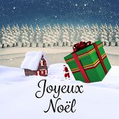 Joyeux noel against snowy landscape with fir trees