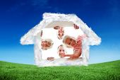 Happy family unpacking boxes against green field under blue sky