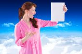 Woman shocked looking at paper against bright blue sky over clouds