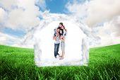 Cheerful parents giving their children piggyback ride against green field under blue sky