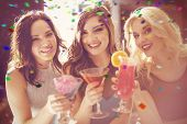 Attractive friends drinking cocktails together against flying colours