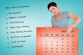 Smiling woman pointing at calendar on a panel against orange card