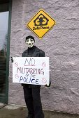 Man In Mask Holds Protest Sign.