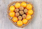 Tangerins And Kiwi Fruit In A Wicker Basket