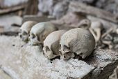 stock photo of coffin  - Human bones and skulls in Ketekesu (Tana Toraja South Sulawesi Indonesia) traditional burial site with semi open old wooden coffins placed in caves or hanging from cliffs.