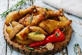 baked chicken leg with potatoes on a wooden surface