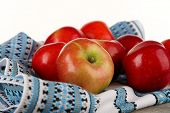 Heap of apples with dish cloth on wooden table isolated on white background