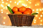 Fresh ripe mandarins in wicker basket, on snow, on lights background