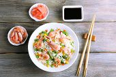 Boiled rice with shrimps and vegetables on wooden background