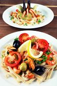 Assortment of Tasty pasta with shrimps, mussels, black olives and tomato sauce on plates on wooden background