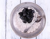 Metal tray with glass bowl of prunes, lace doily and spoon on color wooden background