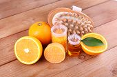 Ripe orange with bottles of bath salt and essential oil, bar of soap and wooden brush on wooden background