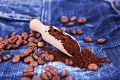 Wooden scoop with ground coffee and beans on jeans background