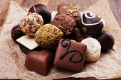Chocolates assorted on crumble paper on wooden rustic background