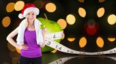Festive fit blonde smiling at camera holding apple against measuring tape