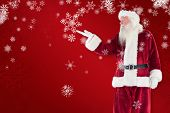 Santa shows something to camera against red snowflake background