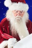 Santa writes something with a feather against blue snowflake background
