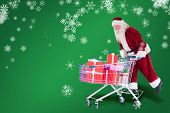 Santa rides on a shopping cart against green