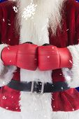 Santa Claus wears boxing gloves against blue snowflake background