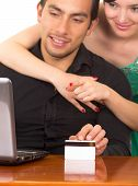 young attractive happy couple in front of computer buying online with credit card