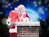 Santa carries a few presents against christmas village under full moon