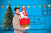 Young man with many christmas presents against blue background with vignette