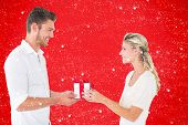 Young couple with gift against red background
