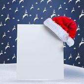 Santa hat on poster against blue reindeer pattern