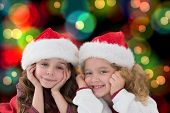 Festive little siblings smiling at camera against colourful glowing dots on black