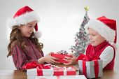 Cute siblings with gifts against christmas tree in bright room