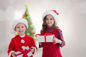 Cute siblings with gifts against blurry christmas tree in room