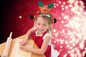 Festive little girl making cookies against light design shimmering on red