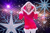 Festive blonde smiling at camera against digitally generated cool nightlife background