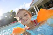 Cheerful 4-year-old girl playing in pool