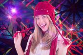 Pretty blonde smiling at camera in warm clothes against digitally generated disco laser background
