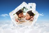 Two friends looking at each other while reading books on a blanket against bright blue sky over clouds