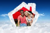 Smiling couple sitting on the grass having picnic together against bright blue sky over clouds