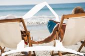 Cute couple holding hands while lying on their deck chairs against house outline