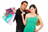 happy young woman holding credit card while unhappy annoyed boyfriend husband carries shopping bags