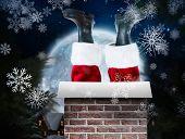 Santa claus boots against christmas village under full moon