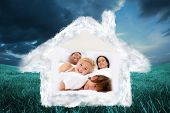 Family realxing in parents bed against blue sky over green field