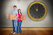 Young couple holding moving boxes against room with wooden floor