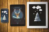 Snow on fir tree against tablet and smartphone on desk