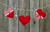 Red hearts and locks hanging from clothesline by rustic wooden fence