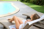 Woman relaxing by pool in long chair