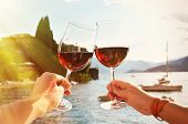 Two wineglasses in the hands. Varenna town at the lake Como, Italy