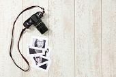 Backround with an vintage camera and some black and white retro photographs on a wooden surface