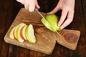 Hands of women cutting apples on board on wooden table background