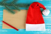 Santa red hat with fir-tree branch, sheet of paper and pencil on color wooden background